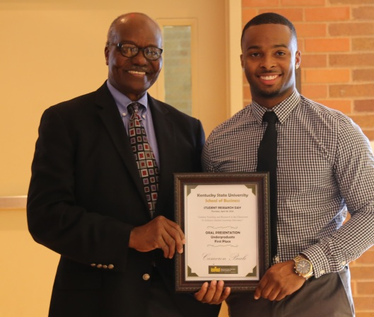 Economics professor Dr. Abdul Turay congratulates Cameron Beale for winning first place in his oral presentation.