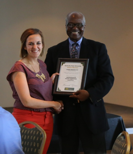 Economics professor Dr. Abdul Turay congratulates KSU student Hannah Gomez for her second-place honor at the Student Research Day ceremony in the Student Center Ballroom.